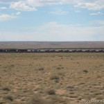 Long train with tanks on it next to Route 66